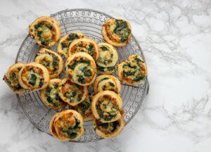 Spinazie kaas rolletjes van bladerdeeg op een afkoelrooster